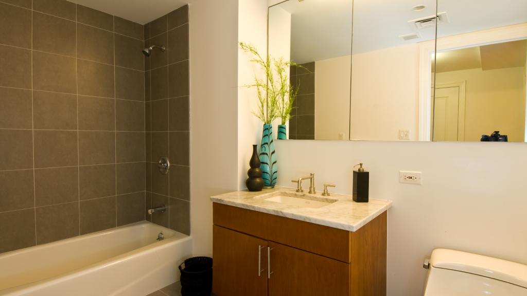 Kuvaa kylpyhuonetta, joka on remontoitu ja värimaailmaltaan lämmin